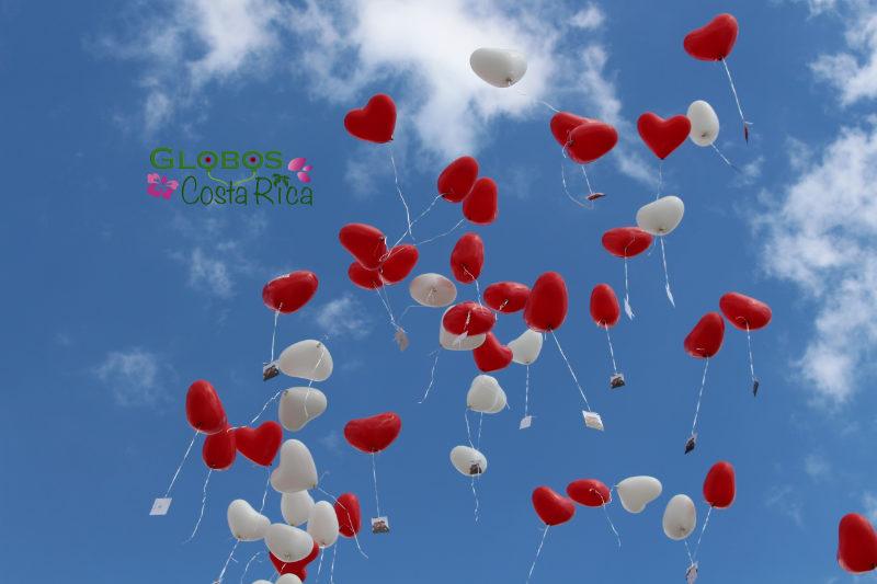 Rote und weiße Helium Herzen steigen in den Himmel für eine Hochzeit in Rohrmoser Costa Rica.