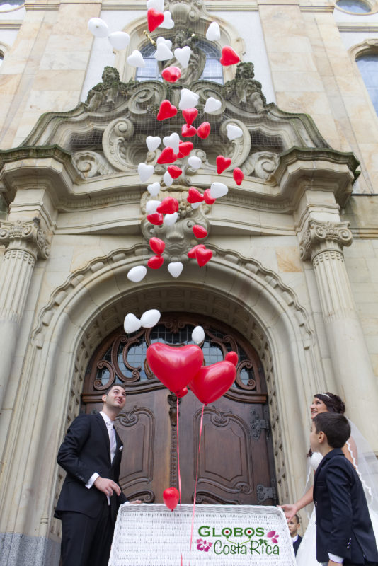 Red and white helium balloon hearts for a wedding in Curridabat.